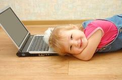 Muchacha de 3 años que mienten cerca de la computadora portátil Fotos de archivo libres de regalías