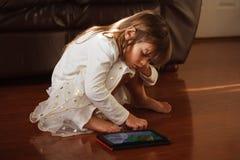 Muchacha de 4 años dulce en el blanco, jugando con el iPad Fotografía de archivo libre de regalías