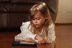 Muchacha de 4 años dulce en el blanco, jugando con el iPad Imagen de archivo