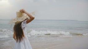 Muchacha de 5-7 años hermosa feliz con el pelo del vuelo y el sombrero de paja grande que corren a lo largo de la playa exótica t almacen de video