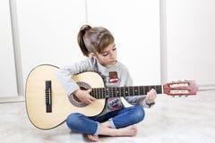 Muchacha de 9 años que aprende tocar la guitarra Imagen de archivo
