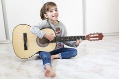 Muchacha de 9 años que aprende tocar la guitarra Fotos de archivo libres de regalías