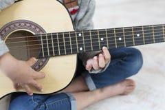 Muchacha de 9 años que aprende tocar la guitarra Fotografía de archivo