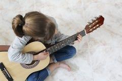 Muchacha de 9 años que aprende tocar la guitarra Foto de archivo libre de regalías