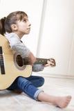 Muchacha de 9 años que aprende tocar la guitarra Imagenes de archivo