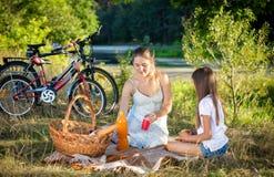 Muchacha de 10 años que tiene comida campestre por el río con la madre joven Fotos de archivo libres de regalías