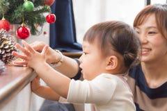 muchacha de 1 años y madre por la ventana en la sala de estar, adornando el árbol de navidad Fotografía de archivo libre de regalías