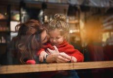 Muchacha de abarcamiento de la madre cariñosa en cafetería Imágenes de archivo libres de regalías