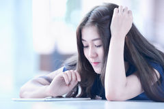 Muchacha de Asia que miente en piso y que mira en la tableta Imagen de archivo