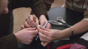 Muchacha de ayuda de la mujer atar el hilo para hacer la muñeca hecha a mano suave en la tabla festival creación manía metrajes