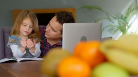 Muchacha de ayuda del padre en sus estudios en sala de estar almacen de metraje de vídeo