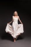 Muchacha de baile en vestido de boda sobre fondo oscuro Imagen de archivo