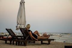 Muchacha de Bali Indonesia que se sienta en la puesta del sol de la playa de Sanur Foto de archivo libre de regalías