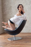 Muchacha de Barelegs que presenta en la silla de cuero Imagen de archivo libre de regalías