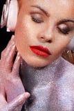 Muchacha de Beautyful con brillo y chispas en su cara y cuerpo Retrato de TDJ atractivo con los auriculares Fotos de archivo