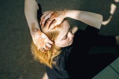 Muchacha de Blondie con un mhendi del modelo en sus manos en la luz del sol Imagen de archivo libre de regalías