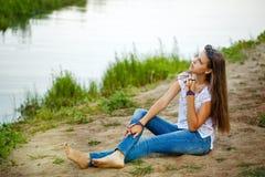 Muchacha de Boho que se sienta en el banco del río Foto de archivo