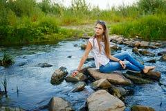 Muchacha de Boho que se sienta en el banco del río Imágenes de archivo libres de regalías