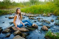 Muchacha de Boho que se sienta en rocas en el río Imágenes de archivo libres de regalías