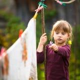 Muchacha de cinco años con el clothespin al aire libre Fotografía de archivo libre de regalías