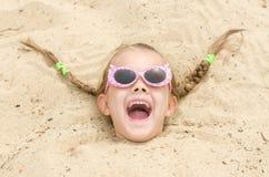 Muchacha de cinco años con los vidrios en una playa derramada en su cabeza en la arena Foto de archivo