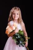 Muchacha de cinco años feliz con un ramo de flores Foto de archivo