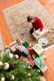 Muchacha de cinco años linda que envuelve un regalo de la Navidad Foto de archivo libre de regalías