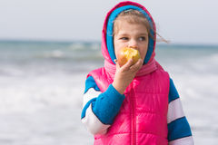 Muchacha de cinco años que come una manzana en el fondo de la costa de mar Imágenes de archivo libres de regalías