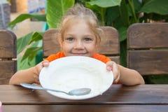 Muchacha de cinco años que muestra la placa vacía para comer Imagenes de archivo