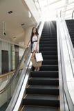 Muchacha de compras asiática en el elevador. foto de archivo