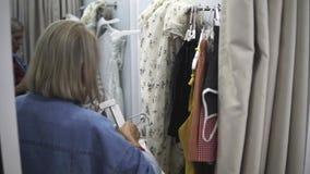 Muchacha de compras Retrato de una mujer hermosa en la tienda de la ropa Muchacha rubia joven con los labios rojos en una tienda  metrajes