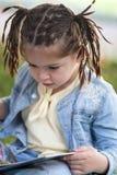 Muchacha de cuatro años con las coletas en una chaqueta azul y un T amarillo Fotografía de archivo libre de regalías