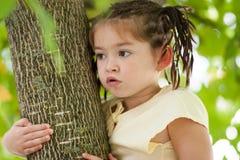 Muchacha de cuatro años divertida con un corte de pelo de muchas coletas en a Imagenes de archivo