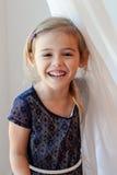 Muchacha de cuatro años feliz por la cortina blanca escarpada Imagenes de archivo