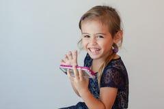 Muchacha de cuatro años feliz que sostiene el teléfono elegante Imagenes de archivo