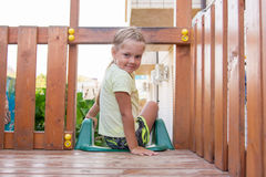 Muchacha de cuatro años que se sienta en complejo personal del juego de la plataforma de madera Fotos de archivo