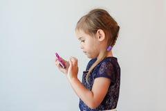 Muchacha de cuatro años seria que golpea ligeramente el teléfono elegante Fotos de archivo libres de regalías