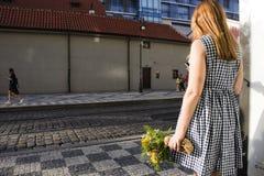 Muchacha de Czechia que sostiene el ramo amarillo de la flor y que espera en la estación del tranvía cerca del centro comercial d Fotos de archivo