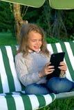 Muchacha de diez años feliz que juega en una tableta en el gardenet imagen de archivo