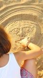 Muchacha de diez años que dibuja una cara impar en la arena imagen de archivo