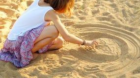 Muchacha de diez años que dibuja una cara impar en la arena fotografía de archivo