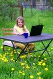 Muchacha de diez años sonriente que juega con el cuaderno foto de archivo