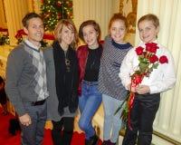 Muchacha de diez años sonriente que se coloca en una escalera roja con los padres y las hermanas de mediana edad Imágenes de archivo libres de regalías