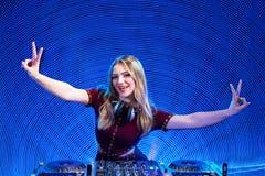 Muchacha de DJ en cubiertas en el partido que gesticula la muestra de V Imagen de archivo libre de regalías