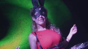 Muchacha de DJ en danza de la máscara de las liebres en la placa giratoria en club nocturno Alineada roja Fingeres del tecleo almacen de video