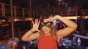 Muchacha de DJ en danza roja del vestido de la máscara de las liebres en etapa en club nocturno Mire in camera metrajes