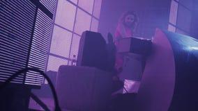 Muchacha de DJ en el baile rojo del vestido de los auriculares en la placa giratoria en club nocturno holidays metrajes