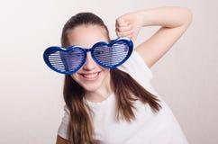 Muchacha de doce años con los vidrios grandes en corazón de la forma Imagen de archivo libre de regalías