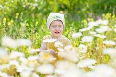 Muchacha de dos años con las flores de la manzanilla Fotos de archivo libres de regalías