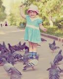 Muchacha de dos años con las palomas Foto de archivo